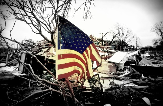 GARLAND, TX - DECEMBER 28: A tattered U.S. flag that had been attatched to a tree waves over the debris at the Landmark at Lake Village North Apartments as the recovery process begins following tornadoes which hit the area late Saturday night December 28, 2015 in Garland, Texas. A meteorolocical assault of tornadoes, blizzards and heavy rain have left dozens dead and a large path of property damage in the Central, U.S. (Photo by Stewart F. House/Getty Images)
